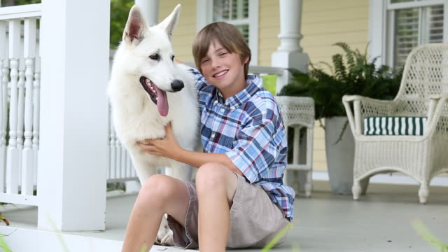 MS Portrait of Young Boy Petting White German Shepherd Dog on Porch of House / Richmond, Virginia, USA