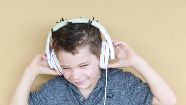 portrait of young boy with headphones and funny hairdo dancing and smiling and pulls headphones off and rests them around his neck. - kelly mason videos 個影片檔及 b 捲影像