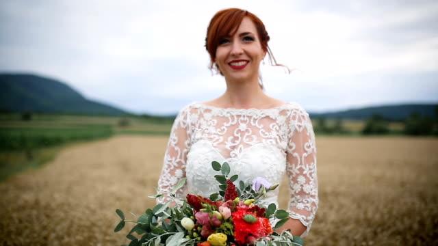 フィールドの若い花嫁の肖像画 - ブーケ点の映像素材/bロール