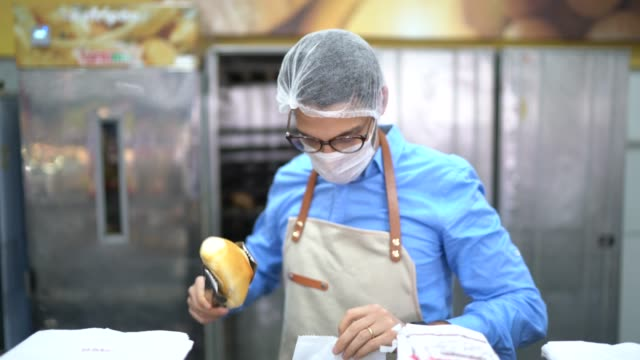 portrait of young business man owner with face mask at bakery - retail occupation stock videos & royalty-free footage