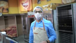 Portrait of young business man owner with face mask at bakery