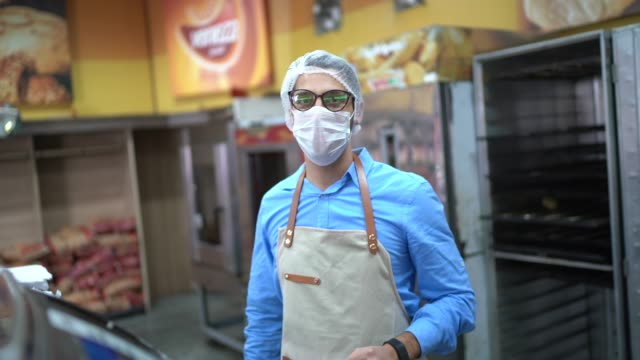 portrait of young business man owner with face mask at bakery - working stock videos & royalty-free footage