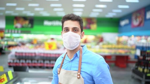 vídeos de stock e filmes b-roll de portrait of young business man owner with face mask at supermarket - serviços essenciais