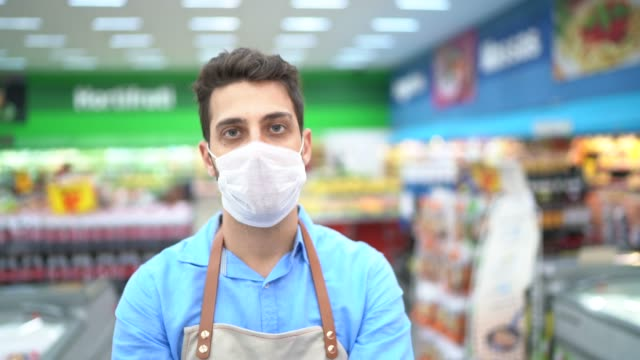 vídeos de stock e filmes b-roll de portrait of young business man owner with face mask at supermarket - funcionário