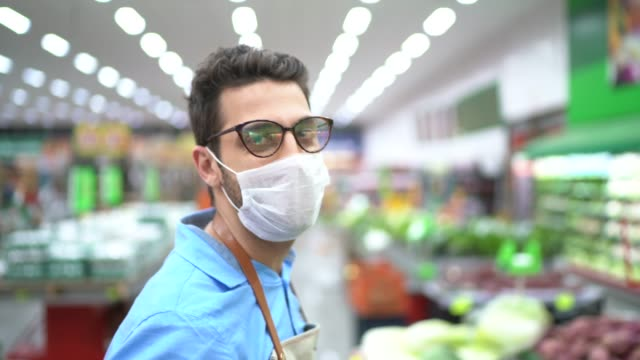 portrait of young business man owner with face mask at supermarket - prevenzione delle malattie video stock e b–roll
