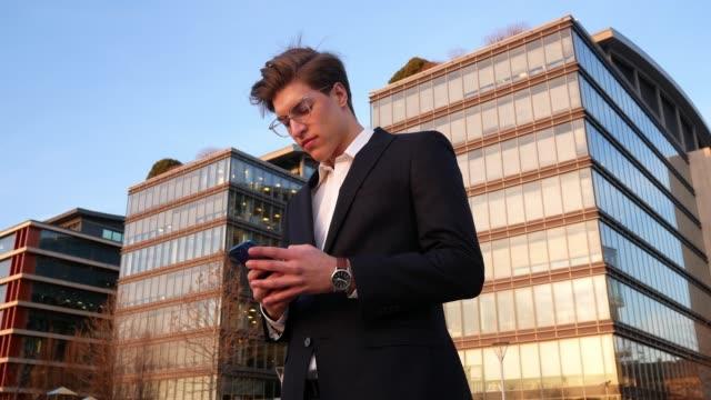 vídeos y material grabado en eventos de stock de retrato de joven empresario en el centro, usando el teléfono - cultura húngara