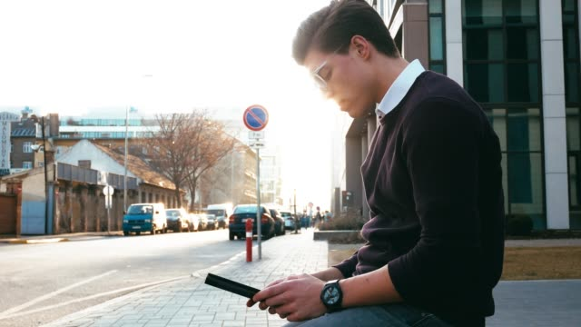 Portrait of young businessman in downtown, using phone