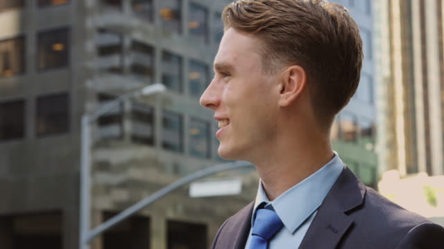 portrait of young businessman outside office building - profile stock-videos und b-roll-filmmaterial
