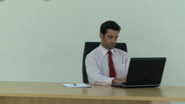 vídeos de stock e filmes b-roll de ms pan portrait of young businessman using laptop at desk in office, cape town, south africa - camisa e gravata