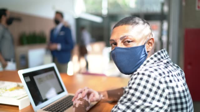 portrait of young businessman using laptop at office's lobby - with face mask - south america stock videos & royalty-free footage