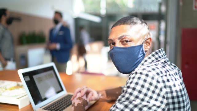 porträtt av ung affärsman med hjälp av bärbar dator i kontorets lobby - med ansiktsmask - sydamerika bildbanksvideor och videomaterial från bakom kulisserna