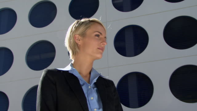 CU LA Portrait of young businesswoman in front of modern office building / Miami, Florida, USA