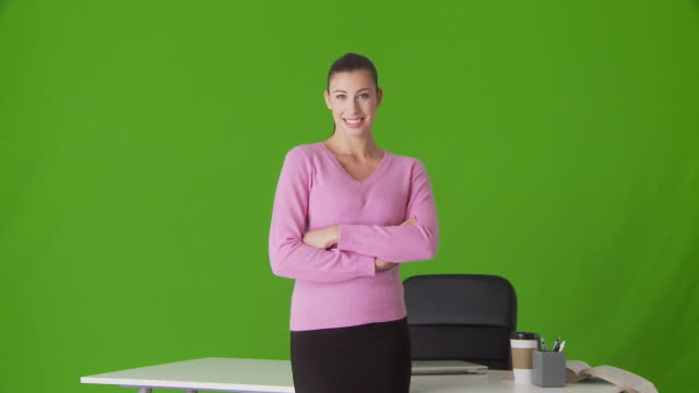 portrait of young businesswoman standing in front of desk - in front of stock videos and b-roll footage