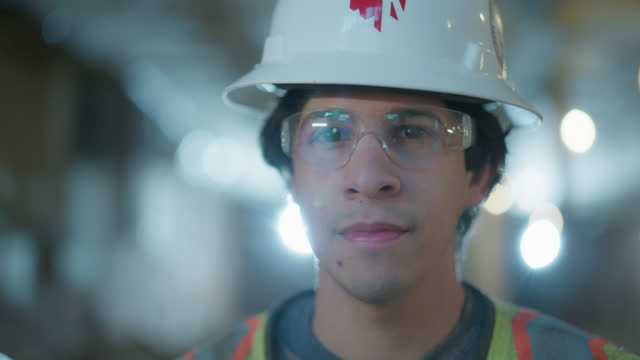 slo mo portrait of young construction worker looking at the camera - engineering stock-videos und b-roll-filmmaterial