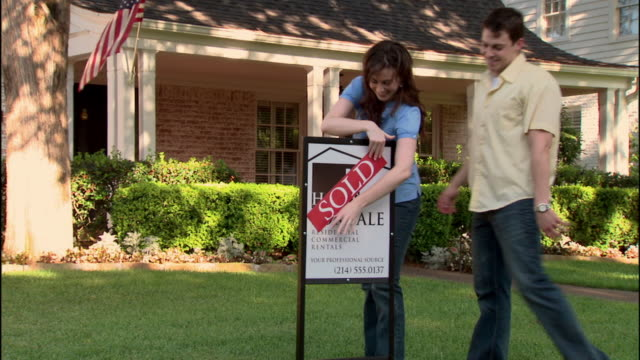 MS, PAN, Portrait of young couple at 'sold' sign in front of brick suburban house, Dallas, Texas, USA
