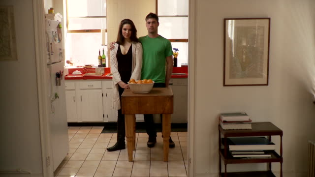 MS ZI ZO Portrait of young couple embracing standing in kitchen, Brooklyn, New York City, New York State, USA