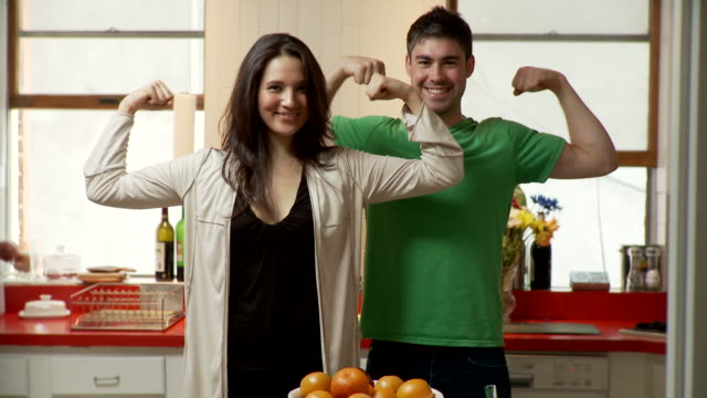 ms portrait of young couple flexing muscles standing in kitchen, brooklyn, new york city, new york state, usa - flexing muscles stock videos and b-roll footage