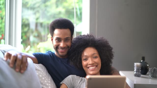 portrait of young couple sharing digital tablet laying in couch - using digital tablet stock videos & royalty-free footage