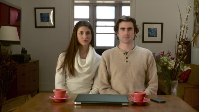ms portrait of young couple sitting at dining table with closed laptop and tea cups / brooklyn, new york city, new york, usa - see other clips from this shoot 1762 stock videos & royalty-free footage