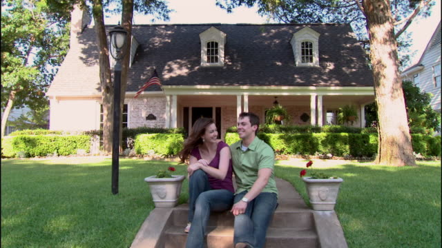 ms, zi, cu, portrait of young couple sitting in front of brick suburban house, dallas, texas, usa - brick house stock videos & royalty-free footage