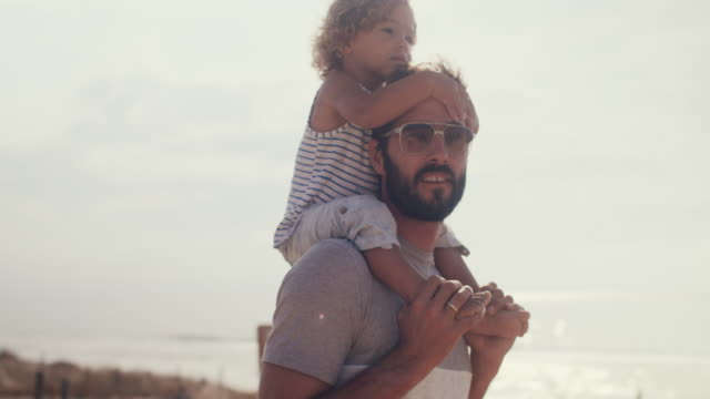 vidéos et rushes de portrait of young father carrying baby boy on his shoulders - famille monoparentale