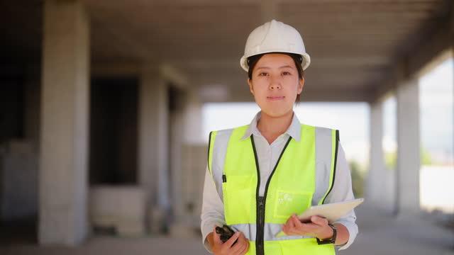 vidéos et rushes de portrait d'une jeune ingénieure tenant une tablette numérique sur un chantier - une seule jeune femme