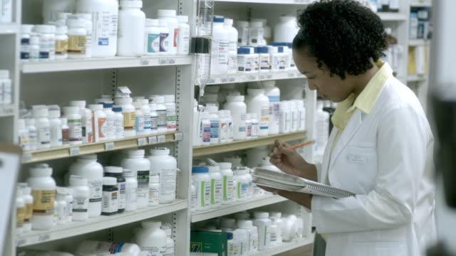 cu, selective focus, portrait of young female pharmacist, scotch plains, new jersey, usa - shelf点の映像素材/bロール