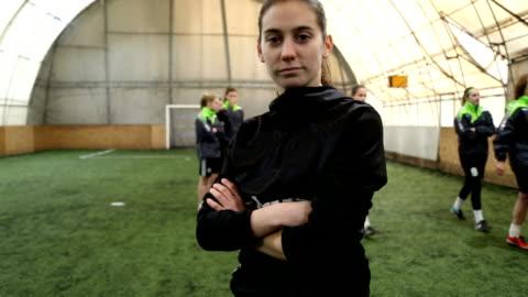 vídeos y material grabado en eventos de stock de retrato de joven futbolista mujer, mirando a cámara con los brazos cruzados - feminidad