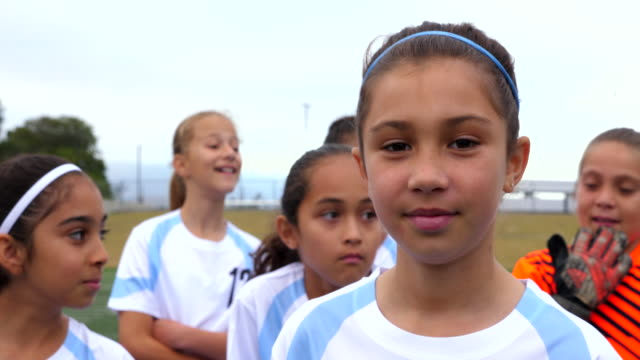 cu portrait of young female soccer player standing on field with team - honesty stock videos & royalty-free footage