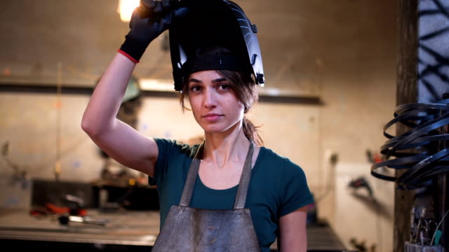 portrait of young female welder - persona di sesso femminile video stock e b–roll