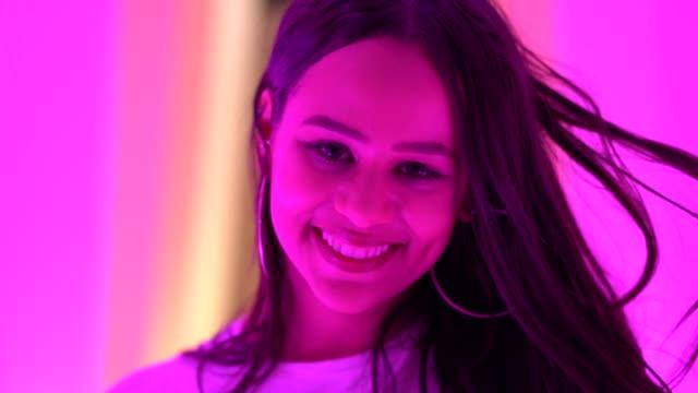 vídeos de stock, filmes e b-roll de retrato de jovem despreocupada em túnel colorido - clubbing