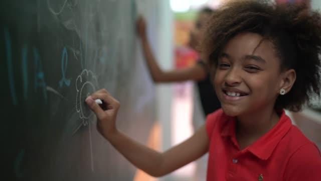 vídeos de stock, filmes e b-roll de retrato de jovem desenhando em quadro-negro em casa - educação