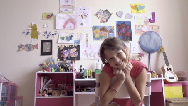 MS Portrait of young girl playing at her desk in her bedroom