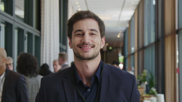 portrait of young handsome businessman at seminar - sorridere video stock e b–roll