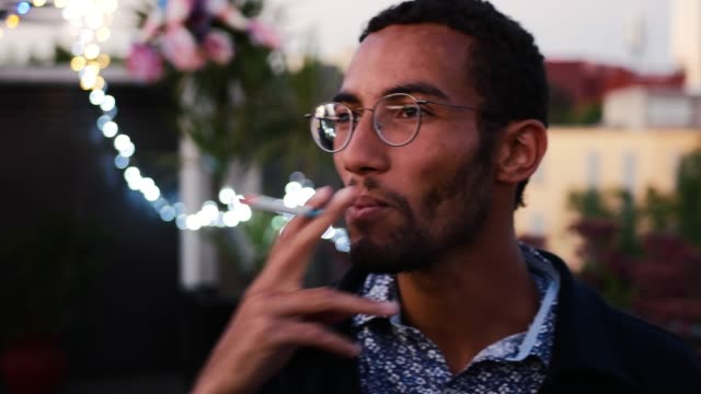 portrait of young handsome mixed race man with eyewear having a cigarette at night - cigarette stock videos & royalty-free footage