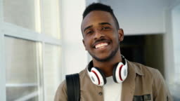Portrait of young handsome student of african-american ethnicity standing in wide white spacious corridor of college with hedphones looking at camera and smiling