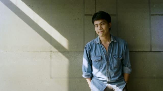 vídeos de stock, filmes e b-roll de retrato do homem asiático feliz novo no fundo cinzento concreto no escritório - povo tailandês