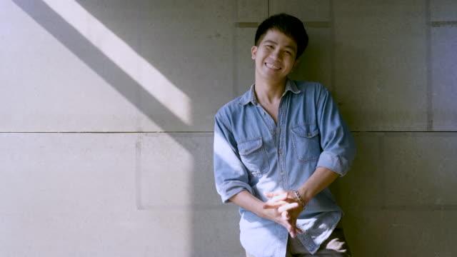 porträt eines jungen glücklichen asiatischen mannes auf betongrauem hintergrund im büro - chinesischer abstammung stock-videos und b-roll-filmmaterial