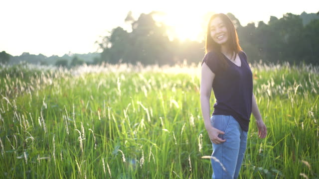 Portrait of young happy woman smiling in field with Sunlight