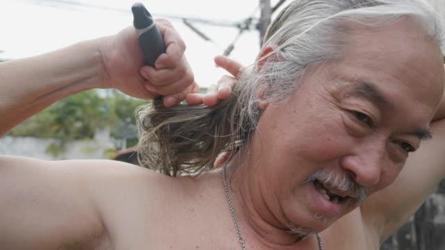 stockvideo's en b-roll-footage met portret van jonge hipster model langharige senior aziatische man met baard kapsel buitenshuis aan te passen. concept: gezond, kapsel, leven. - lang lengte