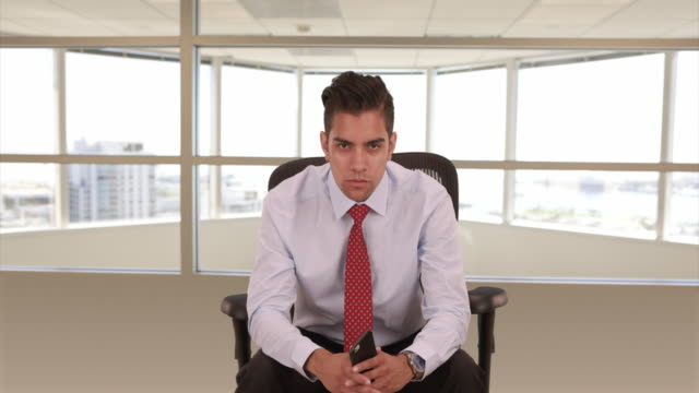 Portrait of young Hispanic business professional sitting in office chair looking at camera