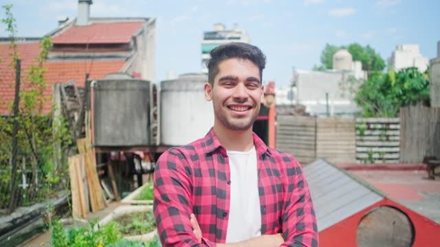 vidéos et rushes de verticale du jeune jardinier hispanique de toit mâle - solution