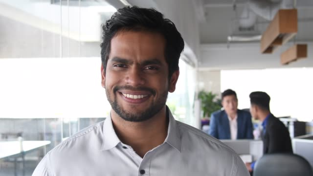 portrait of young indian man in modern office smiling - indian ethnicity stock videos & royalty-free footage