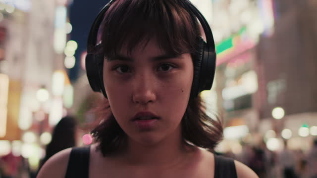 Portrait of young japanese woman with headphones in city at night / Tokyo, Japan