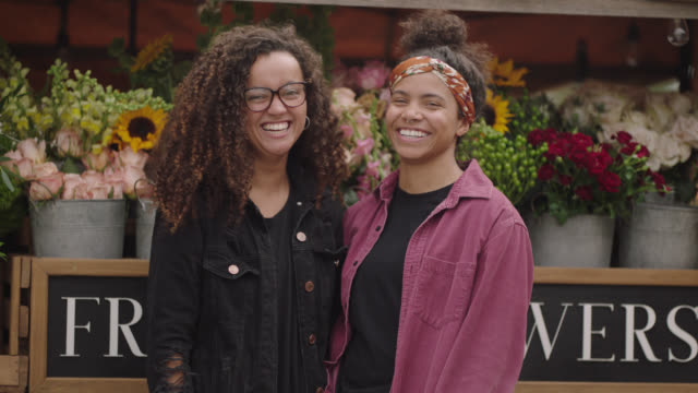 portrait of young lesbian couple flirting and laughing together in front of a mobile flower truck - flower head stock videos & royalty-free footage