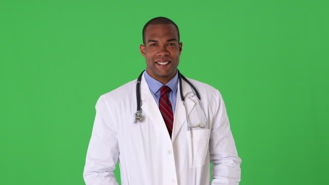 portrait of young male doctor smiling - mezzo busto video stock e b–roll