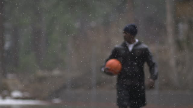 portrait of young man basketball player walking in freezing rain with basketball. - slow motion - sports field stock videos and b-roll footage