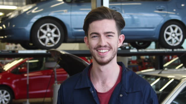portrait of young man in car workshop smiling towards camera - person in further education stock videos and b-roll footage