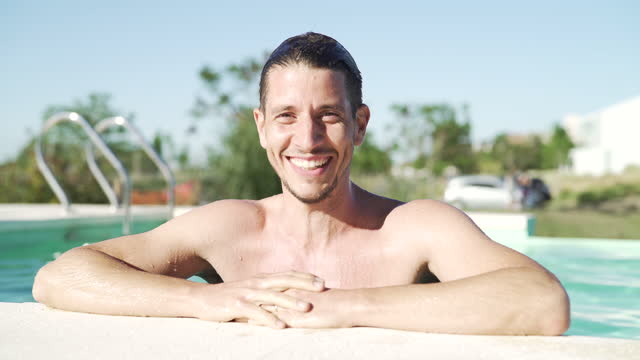 portrait of young man leaning on the edge of swimming pool - bar överkropp bildbanksvideor och videomaterial från bakom kulisserna
