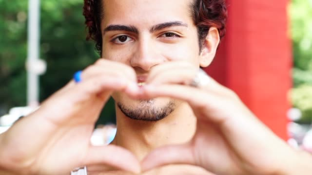 portrait of young man making heart shape with hands - afro video stock e b–roll